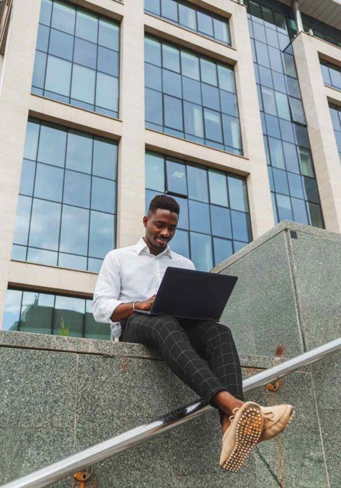 handsome-young-businessman-working-with-laptop-out-778RPJZ-p6sspsluf3m6i070x175t77ezggfzok9eti66azj80 (1)